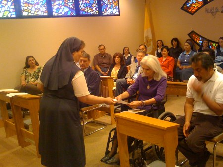 Sr. Madonna Janet gives Carol Anne a Bible to signify the Cooperator's dedication to proclaiming and living Christ